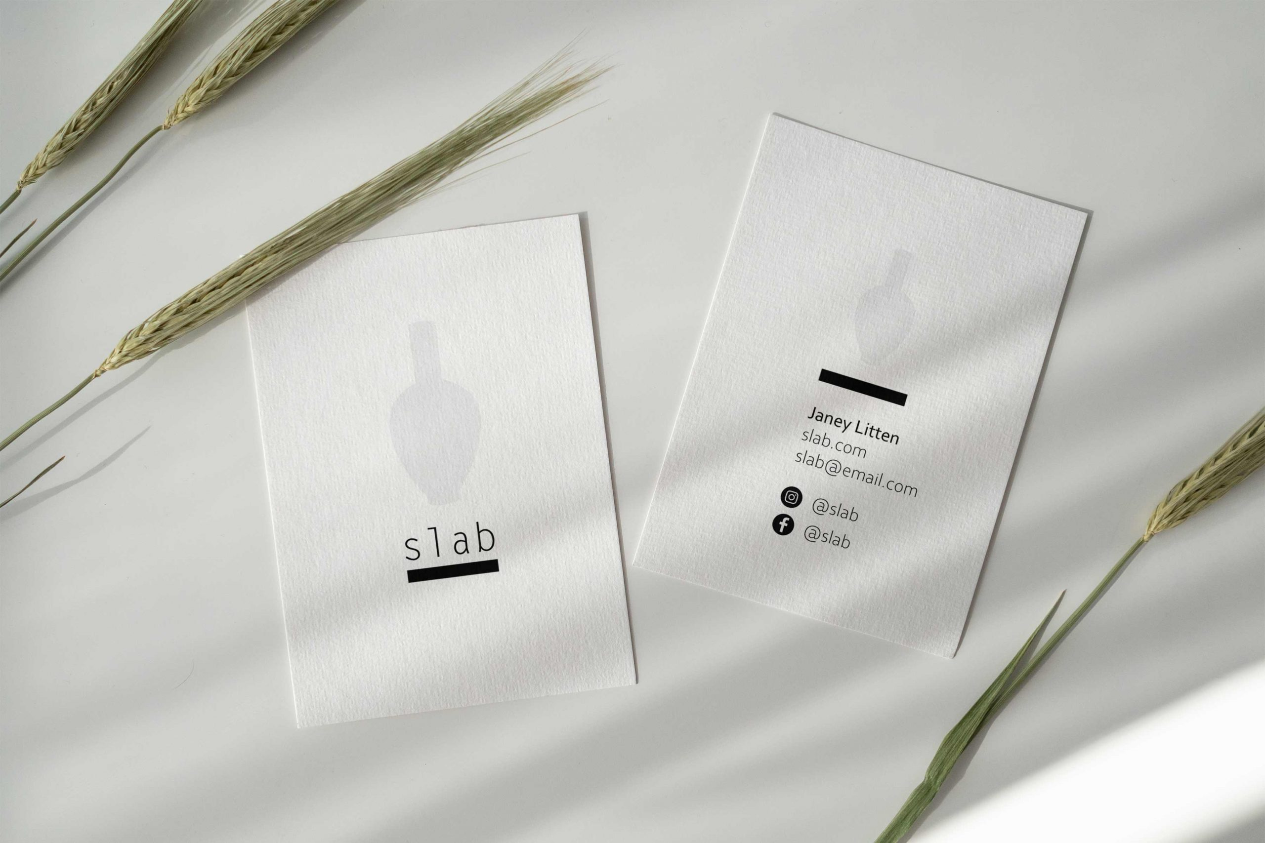 Two business cards with logos designed by Paige Digital and long shadows