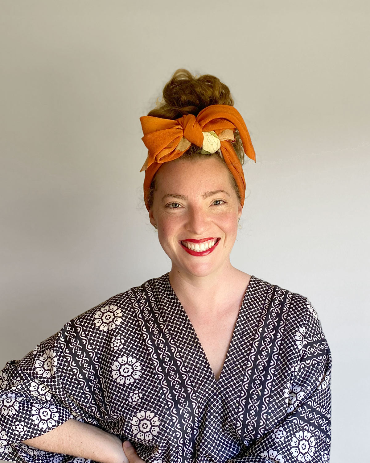 Portrait photo of Candice, wearing an orange scarf, red lipstick and black and white patterned dress with big sleeves