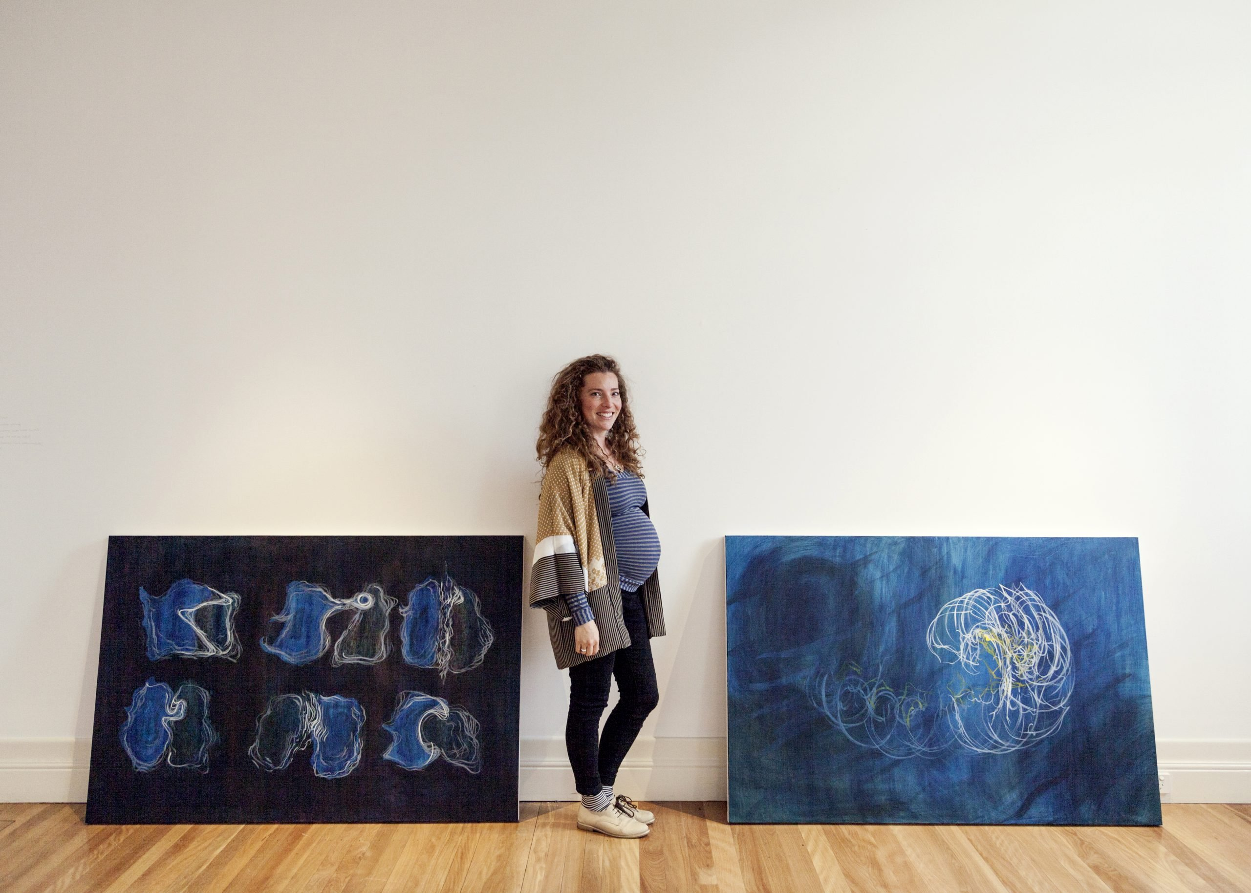 Candice pregnant standing next to two large paintings