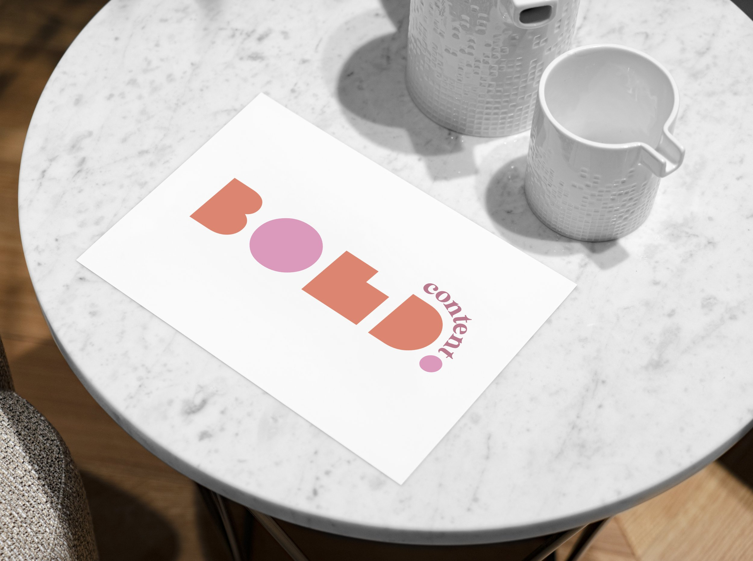 White marble table with BOLD in orange and pink on postcard